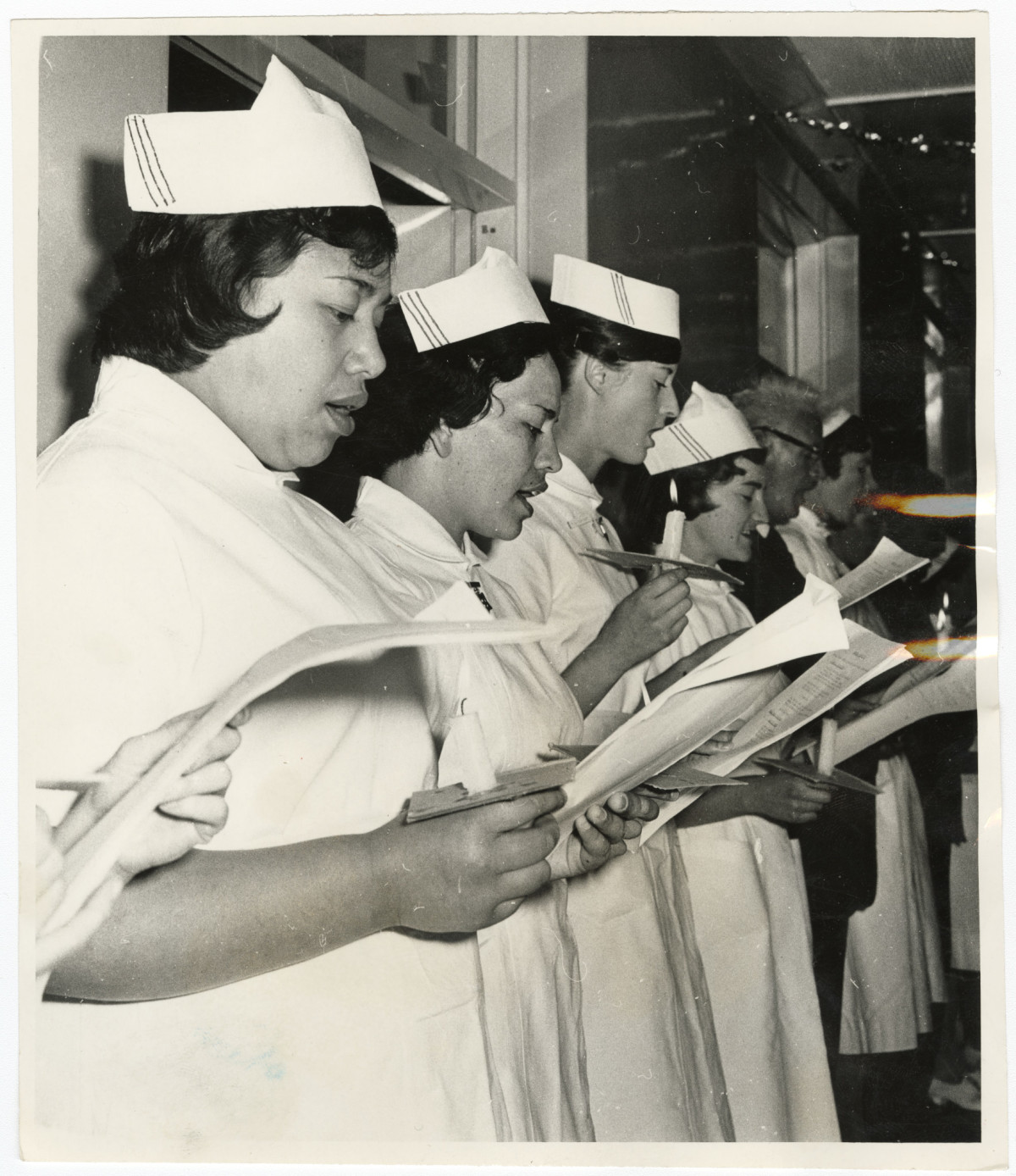 Black and white photo showing a line of nurses singing, 1963