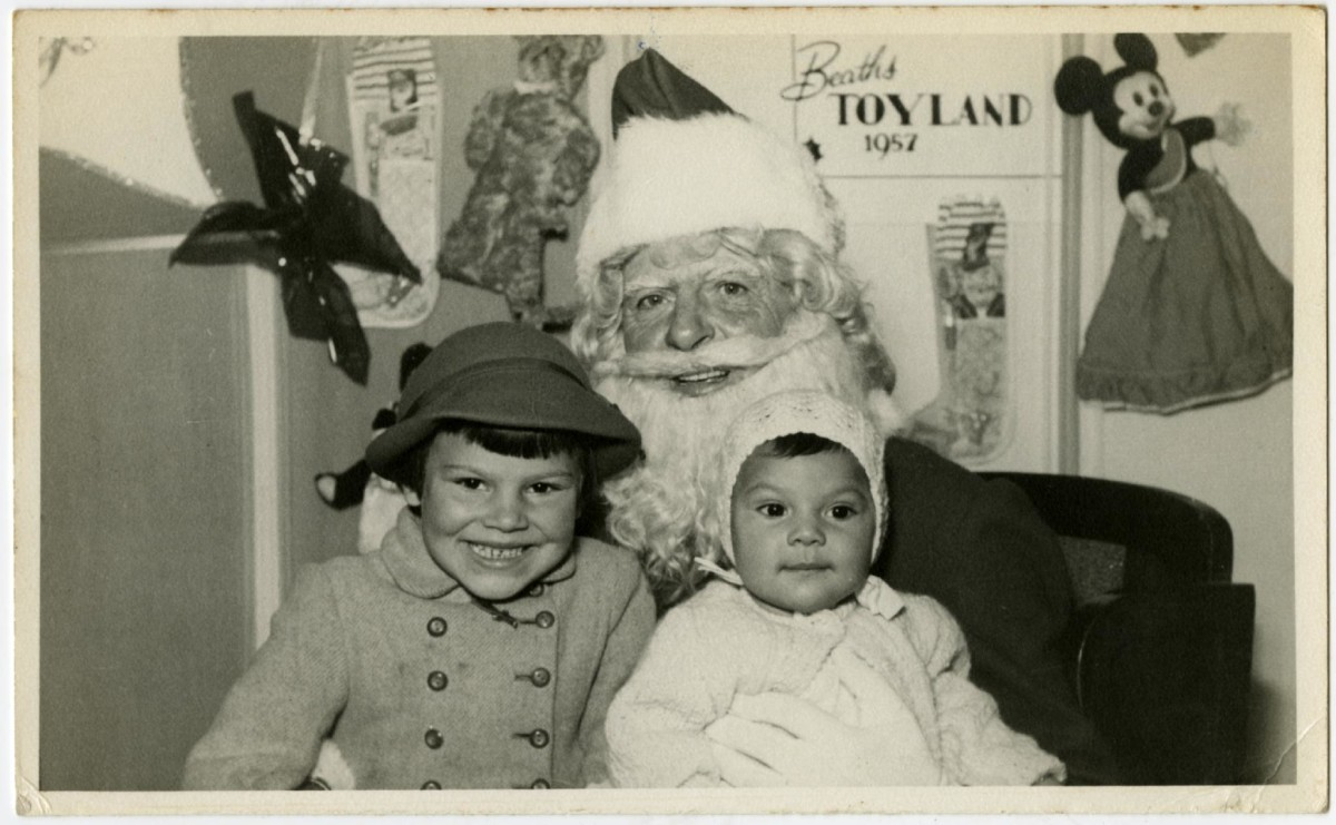 Black and white photo of two children sitting on Santa's knee, 1957