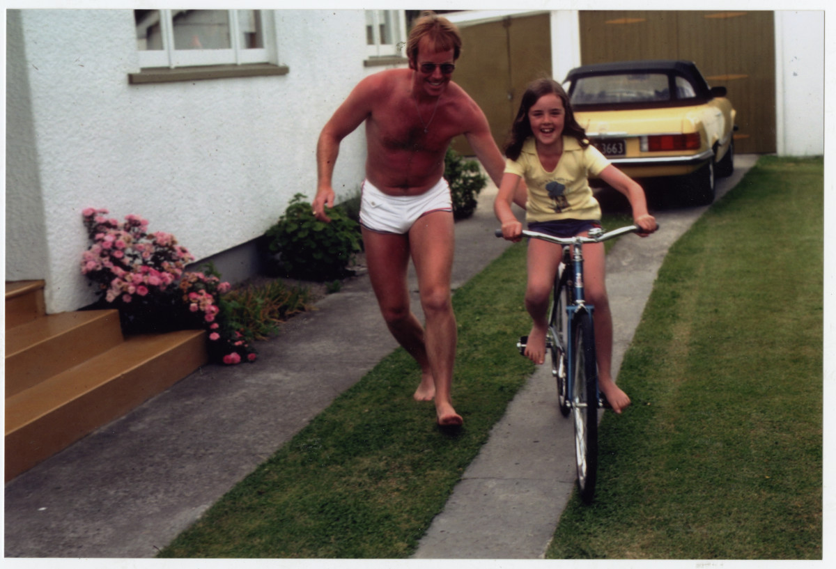 Colour photo of a girl riding a bike in a driveway with a man pushing her
