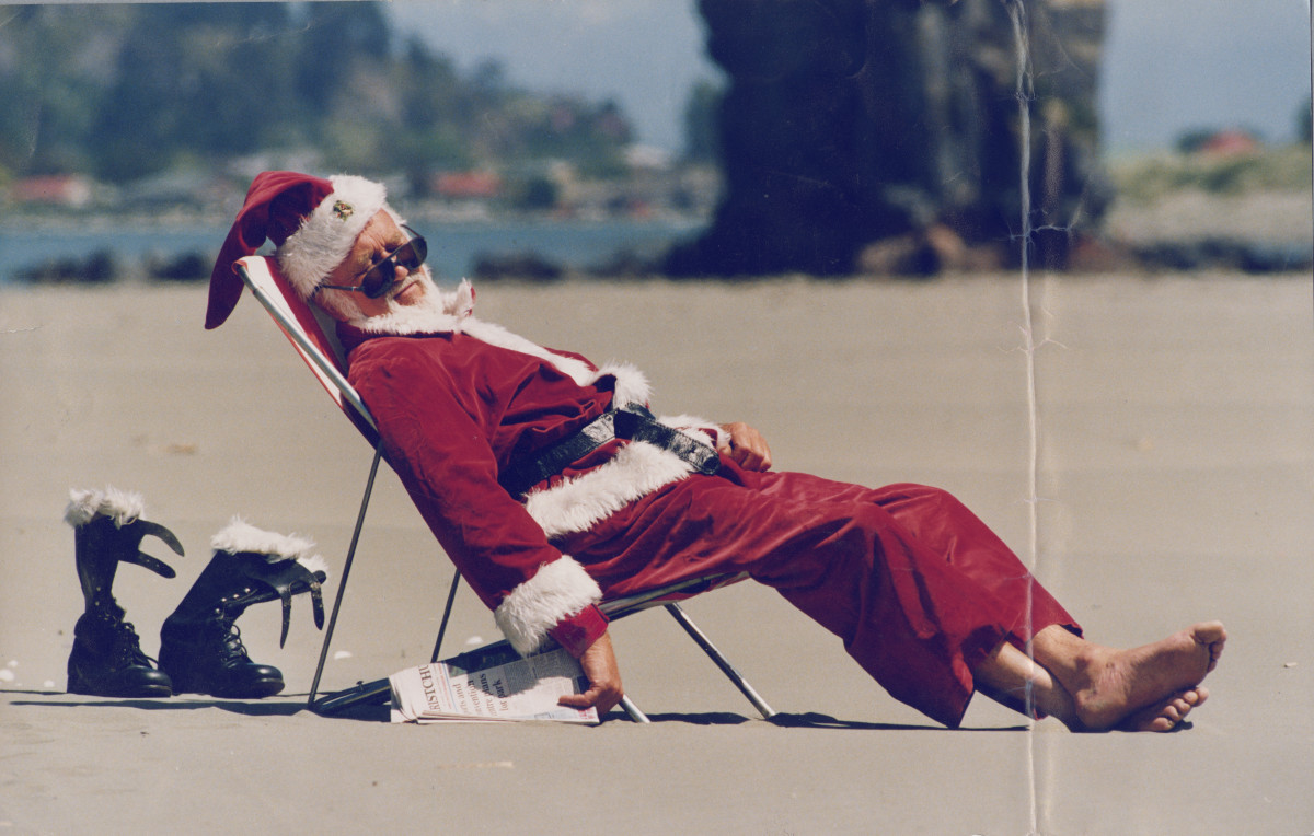 Photo of a man dressed as Santa Claus reclining in a folding chair on a beach