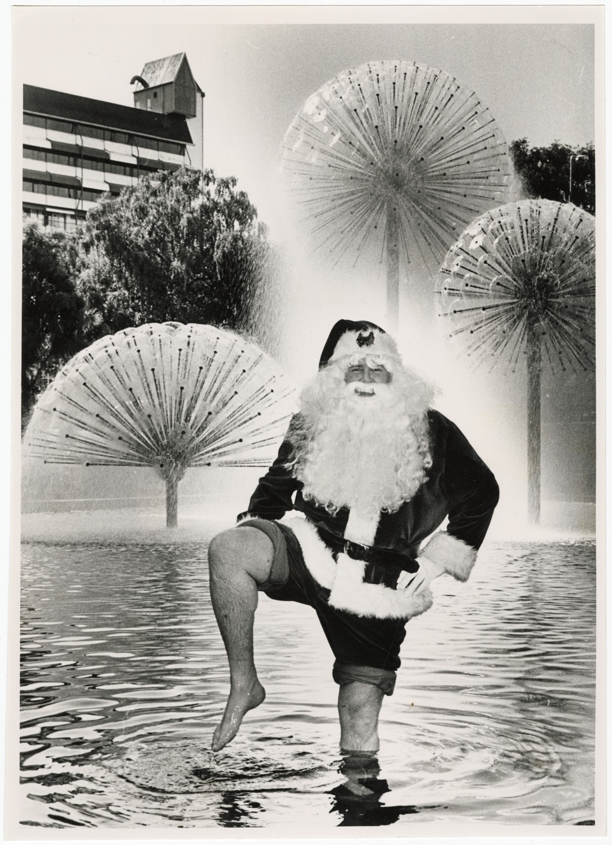 Black and white photo of a man dressed as Santa Claus standing in a fountain, 1984