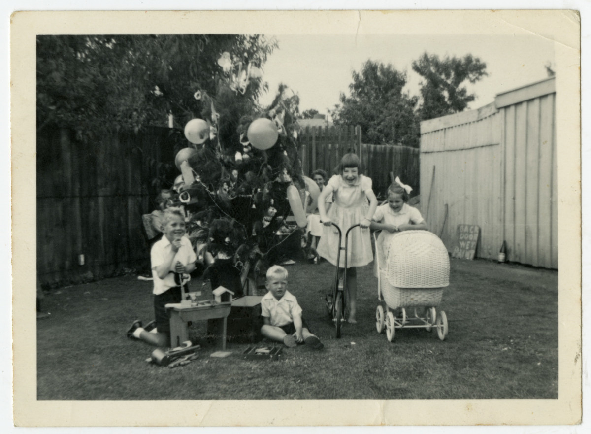 Black and white photo of children and a Christmas tree in a suburban backyard